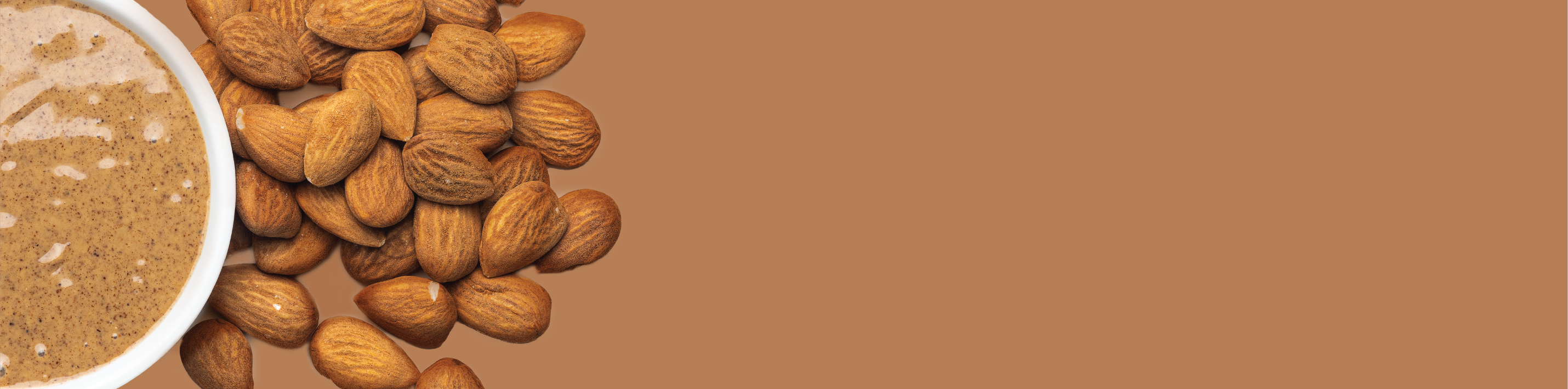 almonds next to almond butter in a bowl